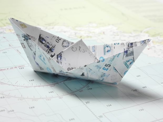 Origami paper boats made of British pounds on a nautical chart